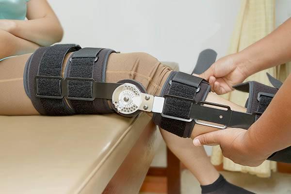 Orthopedist secures leg brace on knee